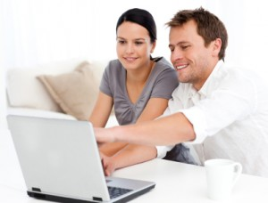 Cute man showing something on the laptop screen to his girlfrien